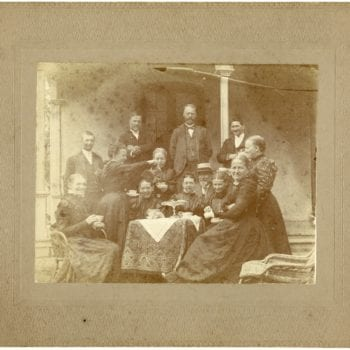Small group of men and women gather for tea outside around table.