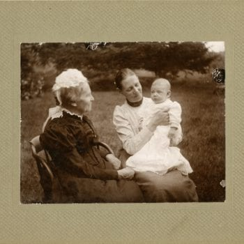 Elderly woman, young woman, and baby sit together outside.