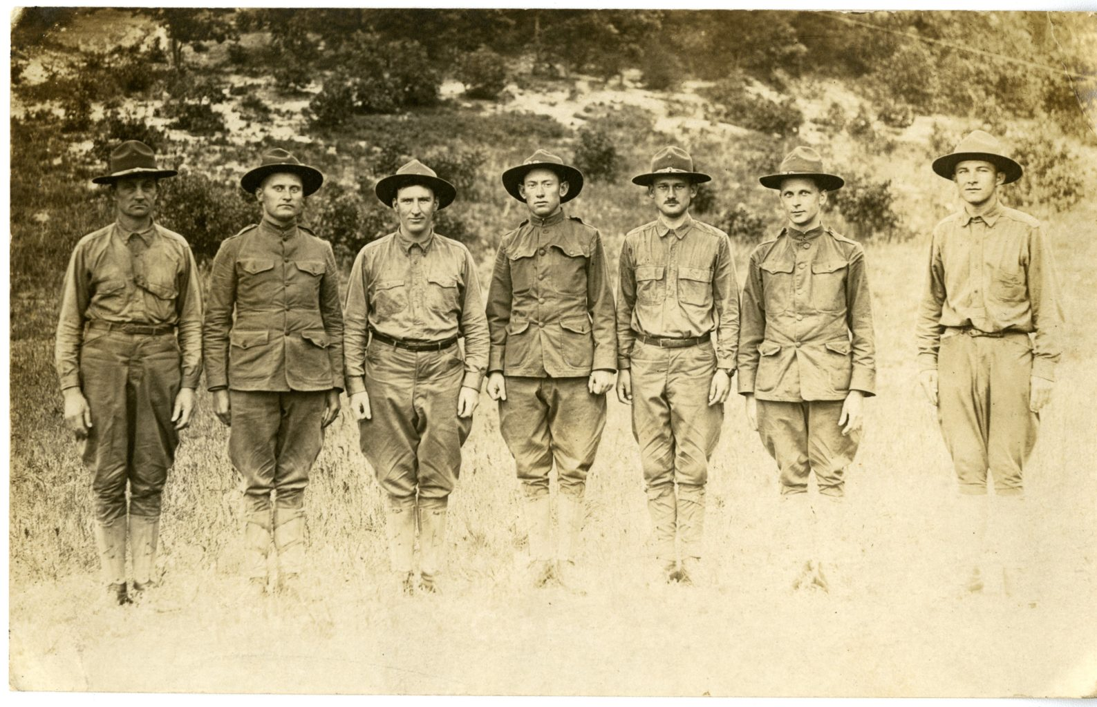 Seven men dressed in uniform stand in a line.