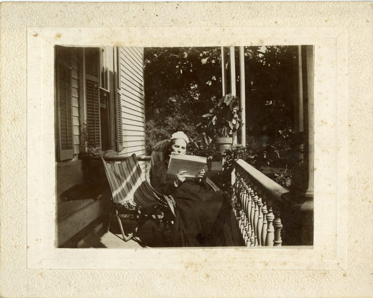 Woman sits on porch reading.