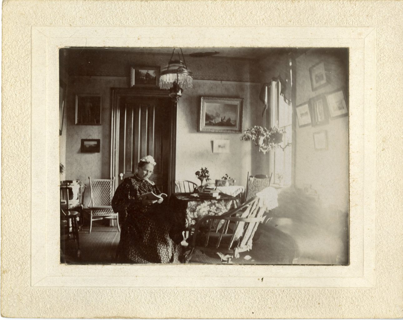 Woman sits inside reading.
