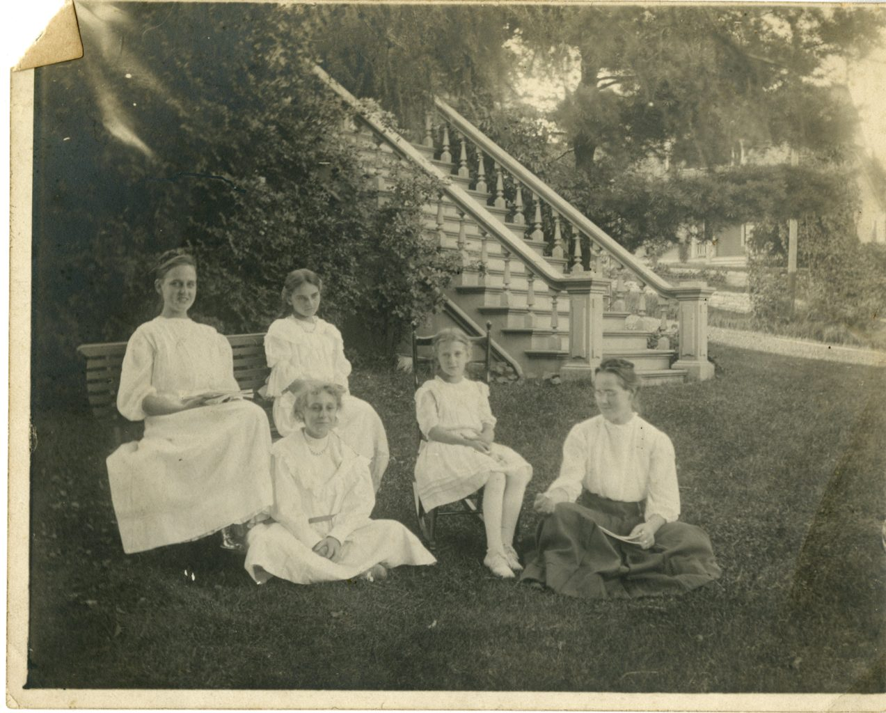 Five young girls sit in a lawn outside of a house.