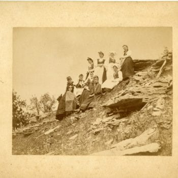 Group of nine women sitting/standing on a hill in Norwegian national dress.