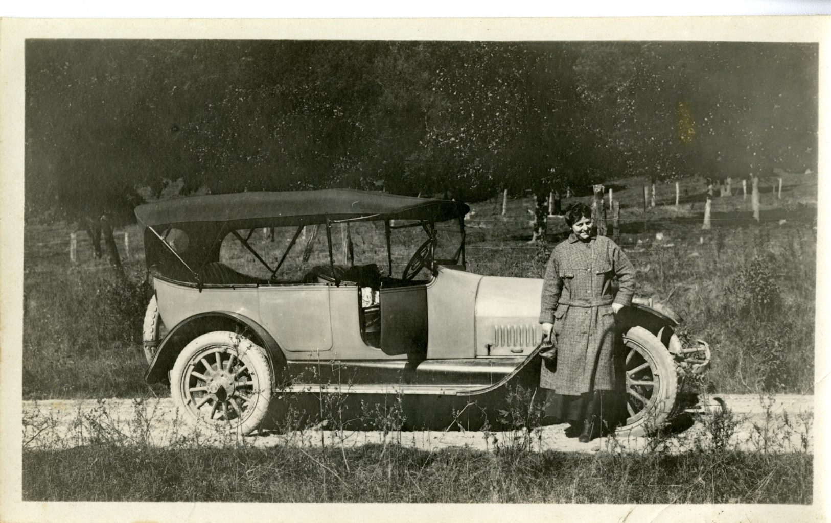 Woman poses by a car on the road.
