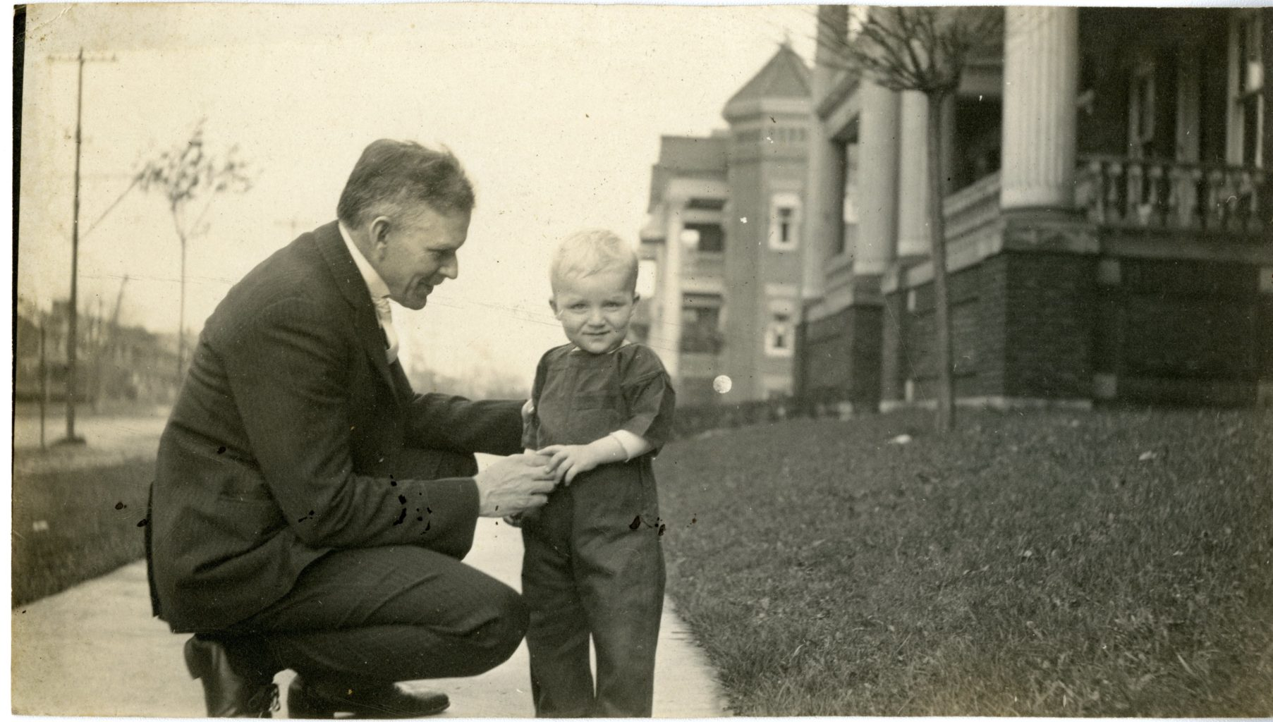 John Koren and male adult pose on a sidewalk.