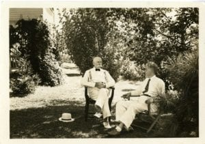 Two men sit outside together.