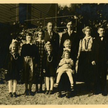 Group photo of family, one female wears Norwegian national dress.