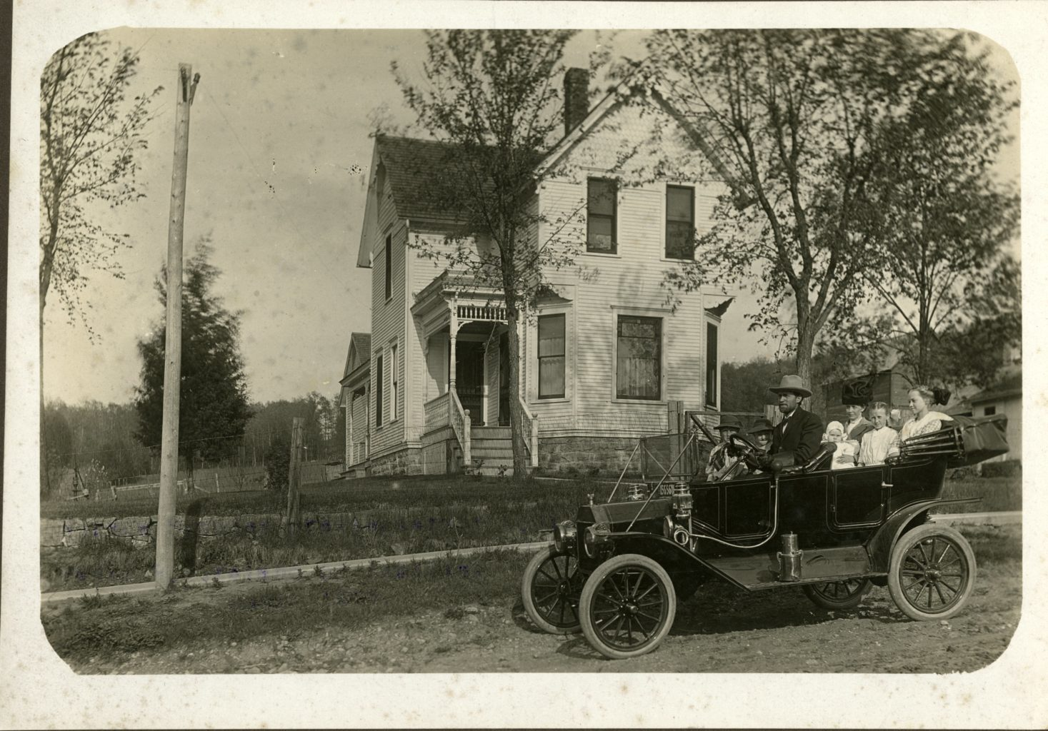 Family in car in front of house.