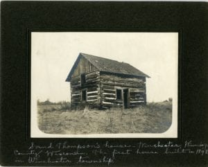Log home in the middle of a field.