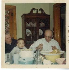 Two older men and young boy sit at the dinner table, the boy blows out a candle on a cake.