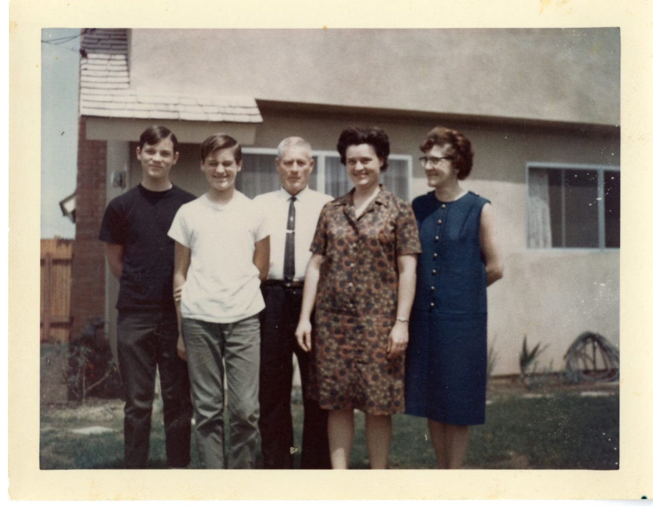 Family of five pose for a photo outside of house.