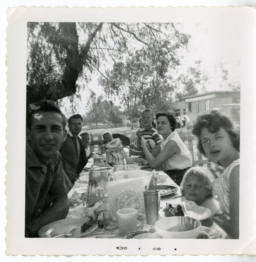 Family of nine sit around a table outside for picnic.