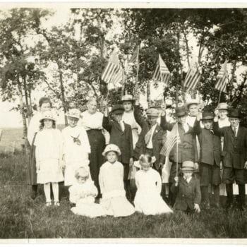 Group of children and one adult pose for a photo with American flags.