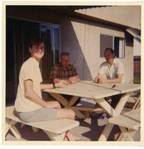 Three men sit around a picnic table.