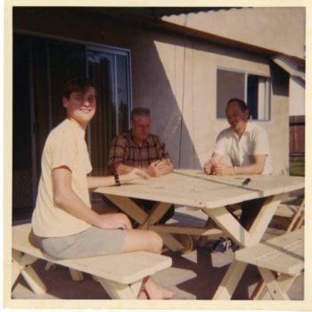 Three men sit around a picnic table.