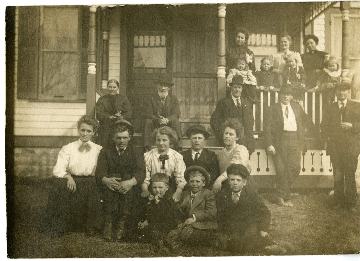 Group of men, women, and children sit outside of a house together.