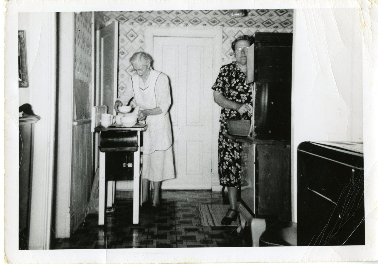 Two women work in the kitchen.
