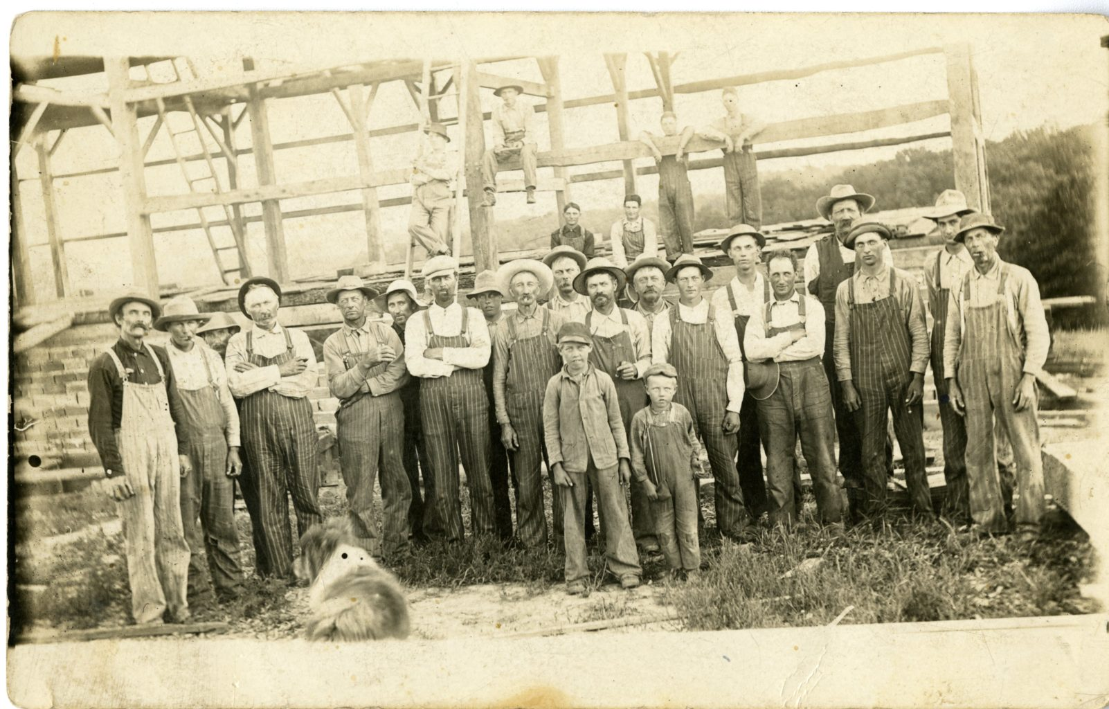 Group of men and boys gather for barn raising.
