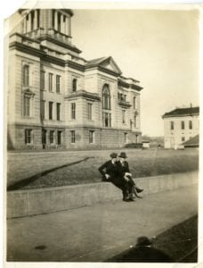 Two men sit outside of the Decorah Courthouse.