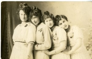 Four girls pose together in the studio.