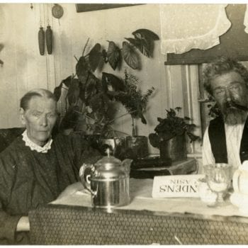 Man and woman sit together inside around a table.