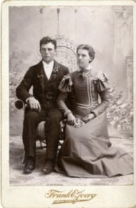 Man and woman pose in a studio.