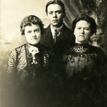 Two women and one man pose in a studio.