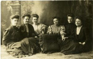 Six women pose in studio.
