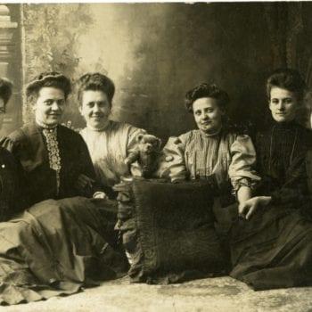 Six women pose in studio.