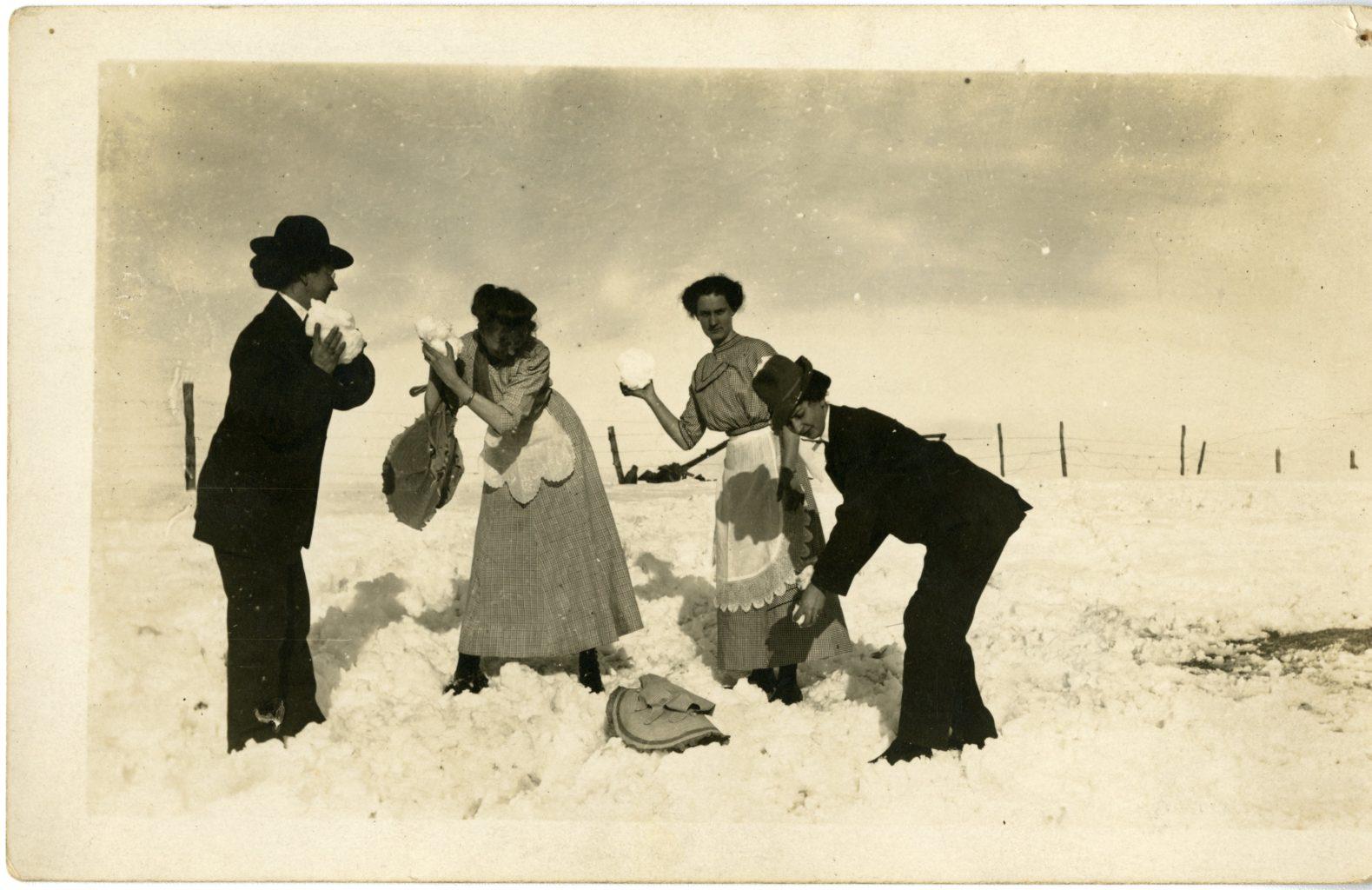Four girls throw snow.