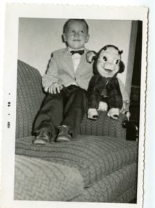 A boy sits on a couch with stuffed animal.